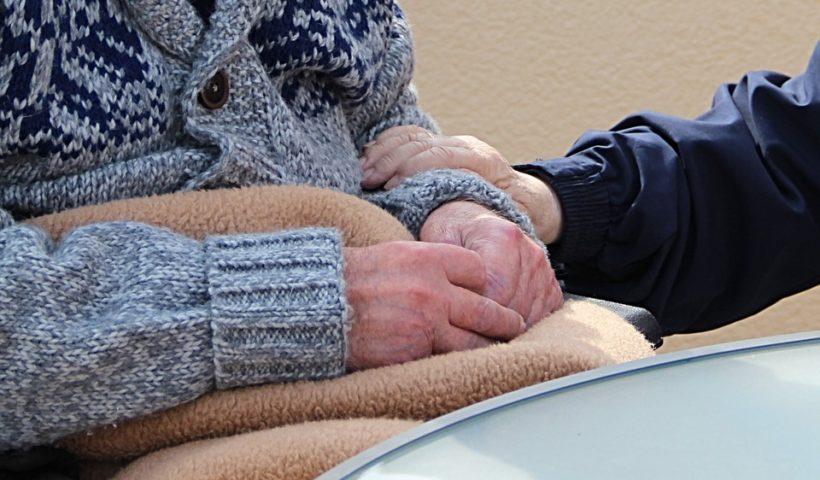 Alter Mensch im Stuhl, helfende Hand hält ihren Arm fest