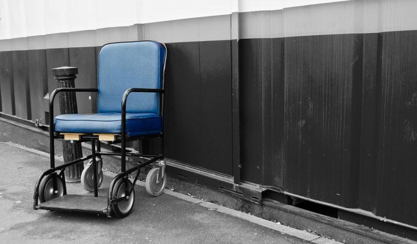 Titelbild, Beitrag. Das Bild zeigt links einen blauen Rollstuhl der an einer dunklen Wand steht.