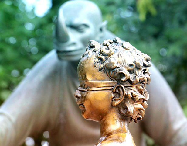 Beitragsbild: Das Bild zeigt den Kopf mit verbundenen Augen vor einer goldenen Figur vor einer Figur mit Horn auf der Nase