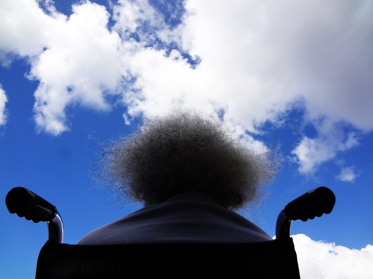Rollstuhl - sitzende Person schaut in den Himmel
